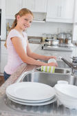 Portrait of a girl washing utensils in kitchen — Stock Photo