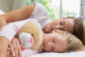 Girl and mother sleeping peacefully with stuffed toy — Stock Photo