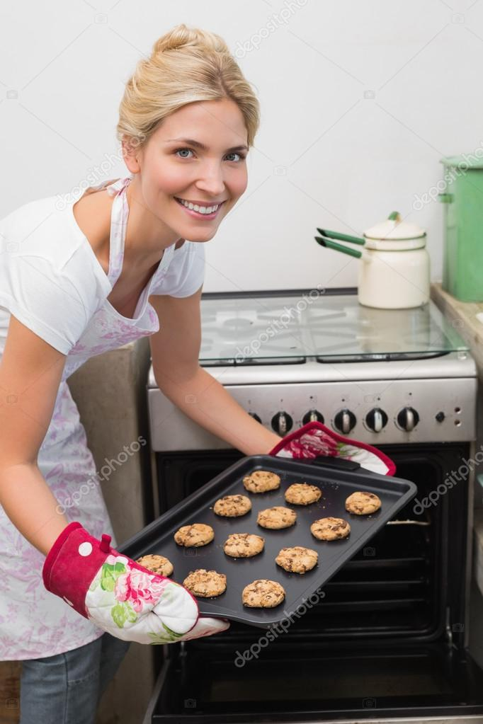 Smiling woman putting a tray of cookies in oven — Stock ...