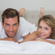 Close-up portrait of a loving couple lying in bed — Stock Photo #42590277