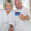 Mature couple holding out credit card at home — Stock Photo