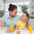 Girl looking at mother while having breakfast — Stock Photo #42590905