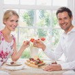 Happy young couple toasting wine glasses over food — Stock Photo
