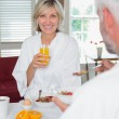 Smiling mature woman having breakfast with cropped man — Stock Photo #42591285