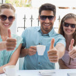 Happy friends gesturing thumbs up in cafe — Stock Photo