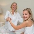 Happy girl and mother holding hands in bed — Stock Photo #42591825