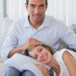 Happy woman resting on mans lap on couch — Photo