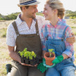 Smiling couple with potted plants in the field — Stock Photo