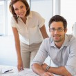 Two colleagues working on blueprints at office — Stockfoto