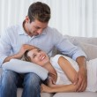 Happy woman resting on mans lap on couch — Foto Stock