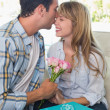 Young man kissing woman with flowers and gift box — Stock Photo #42592519