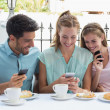 Happy friends reading text message in cafe — Stock Photo