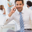 Smiling businessman on call with colleagues at office — Stock Photo #42592765