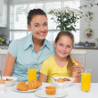 Mother and daughter sitting at breakfast table — Stock Photo #42593249