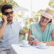 Happy couple with mobile phones at coffee shop — Stockfoto