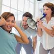 Colleagues yelling through megaphone at businesswoman — Stock Photo #42593615