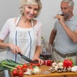 Mature man with wine glass and woman chopping vegetables in kitchen — Stock Photo #42593683