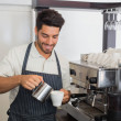 Waiter smiling and making cup of coffee at coffee shop — Stock Photo #42595253