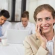 Businesswoman using mobile phone with colleagues at office desk — Stock Photo #42595351
