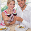 Loving couple with wine glasses sitting at dining table — Stock Photo #42595917