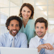 Smiling business people using laptop at office — Stock Photo