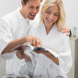 Happy young couple with recipe book in kitchen — Stock Photo #42597111
