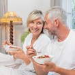 Mature couple having breakfast in bed — Stock Photo #42597225