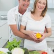 Happy couple preparing food together in kitchen — Stock Photo #42597867