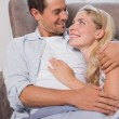 Loving couple looking at each other while lying on sofa — Stock Photo