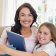Mother and daughter with digital tablet on sofa — Stock Photo #42598397