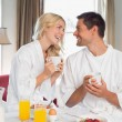 Happy couple looking at each other while having breakfast — Stock Photo