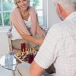 Mature couple playing chess at home — Stock Photo