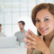 Close-up of a smiling businesswoman with colleagues in meeting — Stock Photo #42599735