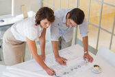 Business people working on blueprints at office — Stock Photo
