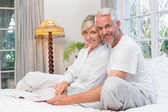 Portrait of a relaxed happy mature couple with book in bed — Stock Photo