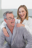 Loving couple in bathrobes in kitchen — Stock Photo