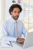 Portrait of businessman using laptop at office desk — Stock Photo