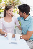 Smiling couple with coffee cups at cafe — Stock Photo