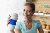 Smiling woman with coffee sipper in coffee shop — Stock Photo