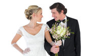 Newlywed couple with bouquet looking at each other — Stock Photo