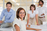 Smiling young businesswoman with colleagues at office — Stock Photo