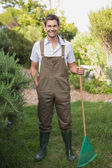 Young man in dungarees holding rake in garden — Stock Photo