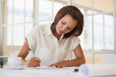 Businesswoman working on blueprint in office — Stock Photo
