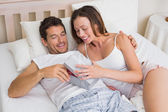 Couple with gift box lying together in bed — Stock Photo