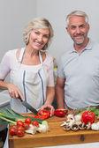 Feliz casal maturo preparando comida na cozinha — Fotografia Stock