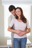 Loving young man embracing woman from behind — Stock Photo
