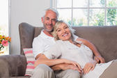 Portrait of a relaxed mature couple sitting on couch — Stock Photo
