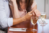 Mid section of woman showing engagement ring with wine glasses o — Stock Photo
