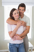 Loving man embracing woman from behind at home — Foto de Stock