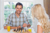 Couple playing chess while having orange juice at home — Stockfoto
